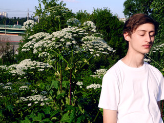 Portrait of a young guy model looks among the green plants