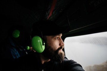 Young man in headset sitting in cockpit