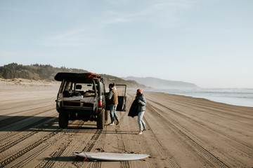 Two people on the beach with their car