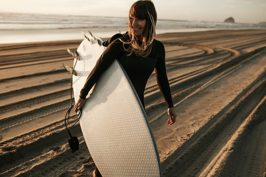 Smiling woman with surfboard walking on beach during sunset