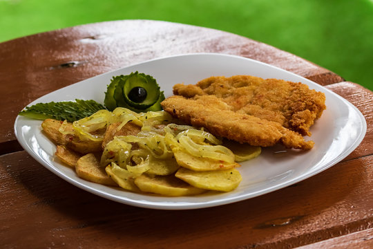 Home-style fried potatoes and a large piece of meat on a white plate. Curly chopped green cucumber. On a wooden table.