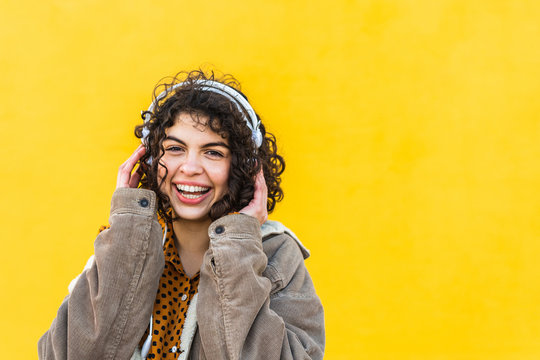 trendy young woman with headphones on street