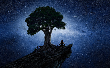 Yoga woman under a tree in front of the universe