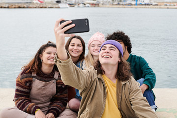 Cheerful friends taking selfie on pier