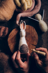 Man's hands making Easter rabbit with wool and felt