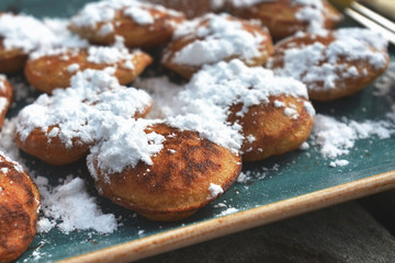 'Poffertjes', a traditional Dutch batter treat dish resembling small, fluffy pancakes, served with powdered sugar and butter