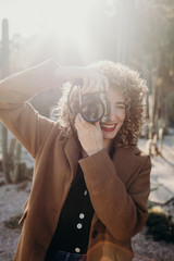 Portrait of beautiful curly blonde woman taking photos with film camera