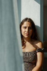 Portrait of young woman standing in sunlight behind curtain