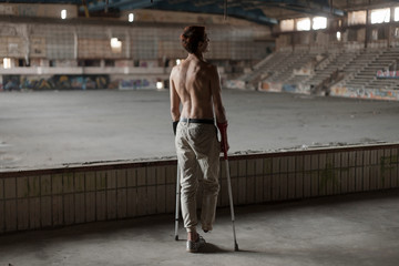 the guy is disabled without legs on crutches standing on the podium in an abandoned sports hall. back to camera