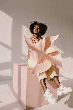 Cheerful black woman with pinwheel sitting on cube