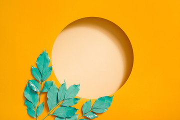 Creative layout made with leaves on bright orange background