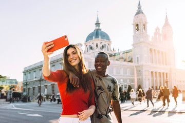 Happy Couple taking selfie in front of Classic building in Madri