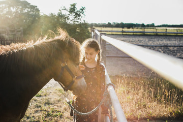 Girl petting pony on ranch