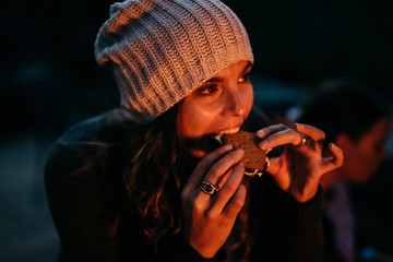 Woman eating S'mores at night by campfire