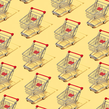 Pattern of shopping carts and shadows on a yellow background. Buying a layout. Flat lay