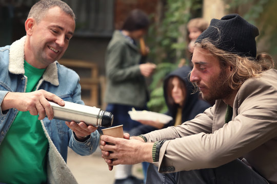 Volunteer giving drink to homeless man outdoors