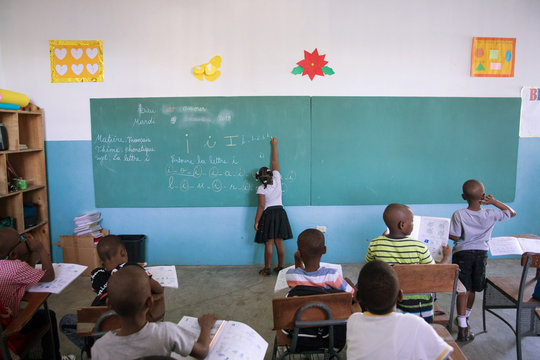 A student writes on the black board during a lesson at the College Saint Pierre-Eglise Episcopale D'Haiti as schools and businesses tentatively reopen their doors, in Port-au-Prince
