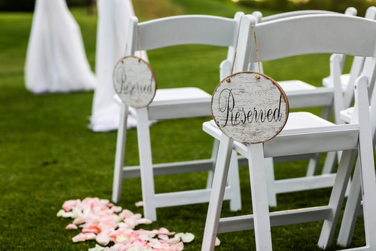 reserved sign on white chair at wedding ceremony