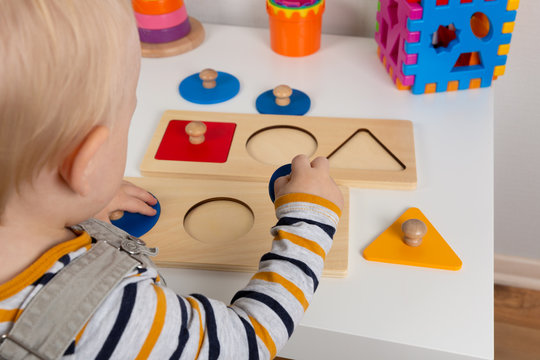 Child works with Montessori material for fine motor skills, sensory play. Playing children with geometry figures