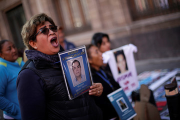 Women hold photographs of their missing relatives during a protest in front of the National Palace in Mexico City