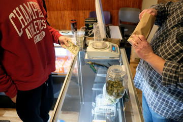 An employee measures from a jar of marijuana on sale at the Greenstone Provisions in Ann Arbor