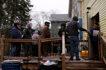 People line up outside of a dispensary after it became legal in the state to sell recreational marijuana in Michigan