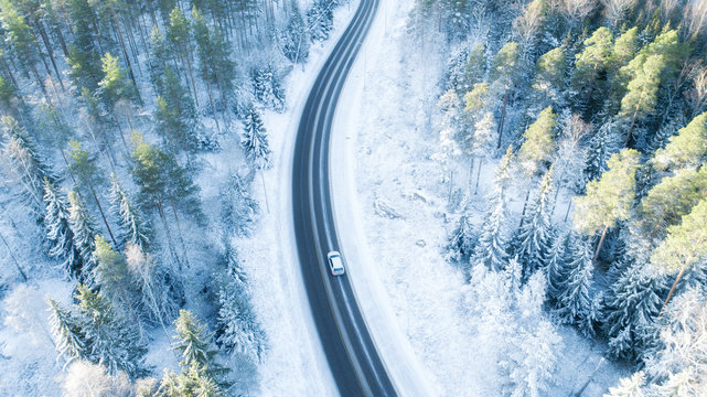 White car drives empty road in forest in the cold Finnish winter. Tourists on road trip cruising through the idyllic snow covered countryside and woods.