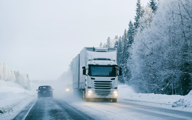 Winter road with snow. Truck in Finland. Lorry car and cold landscape of Lapland. Europe forest. Finnish City highway ride. Roadway and route snowy street trip. Delivery in downhill driveway driving