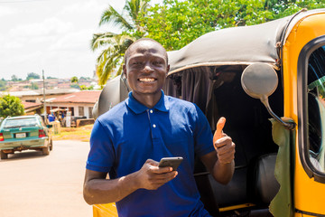 cheerful african man standing next to his tuk tuk taxi smiling and using his smart phone giving a thumbs up