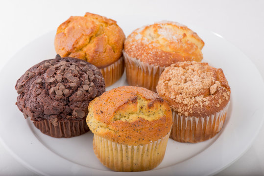 Assortment of freshly baked muffins on a white plate with isolated background