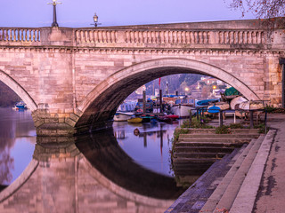 Cloese-up view of the historic Richmon bridge upon Thames and English old boats moored on the river edge in London
