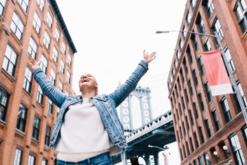 Woman with cancer bandana and raised arms at Manhattan Bridge in New York, USA