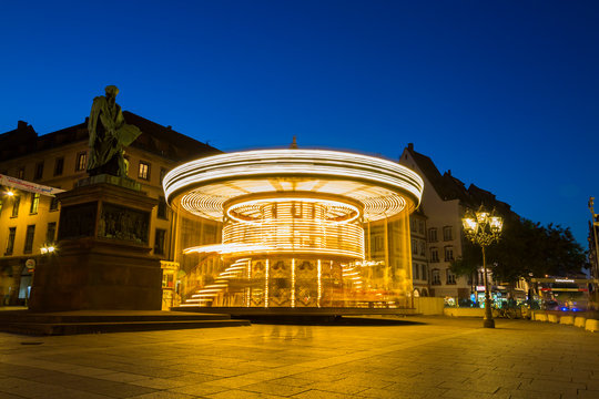 Blurred motion of illuminated carousel against clear blue sky at Amusement Park, Strasbourg, France