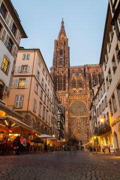 Road amidst buildings against Notre Dame de Strasbourg at sunset, France