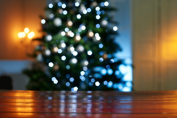 Close-up of wooden table with illuminated Christmas tree in background at home