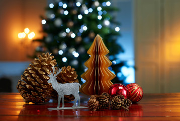 Close-up of various decorations on wooden table with illuminated Christmas tree in background at home Fotobehang