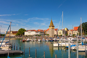 Boats moored at harbor with buildings in background against blue sky, Lindau, Germany