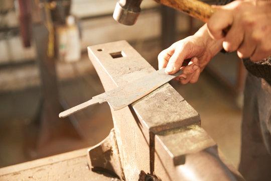 Man finishing blade on an anvil