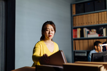 Young woman looking at files in office