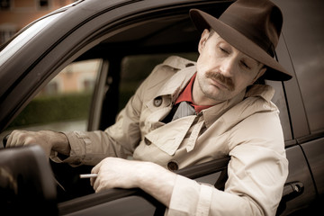 Detective smoking a cigarette in his car while stalking