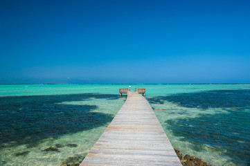 Diminishing perspective of pier in Lac Bay against clear blue sky at Bonaire, Netherlands Antilles Fotobehang