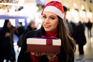 Young woman giving you a gift for Christmas