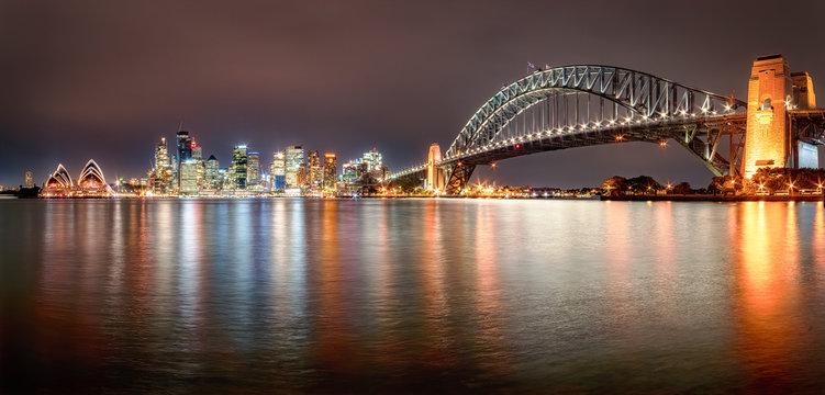 Panoramic shot of illuminated Sydney Harbor Bridge over river against sky at night, Sydney, Australia