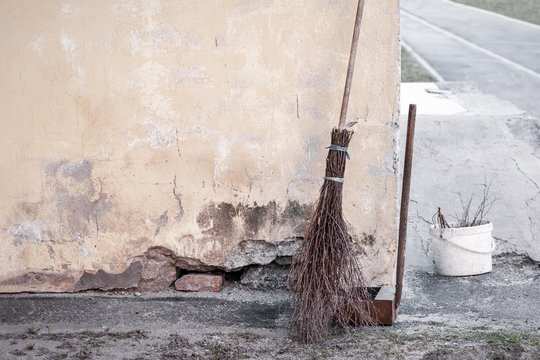 Old shabby wooden broom, rusty scoop and plastic bucket with cut tree branches near the wall of a block house. Janitor inventory. Unskilled and low paid labor concept. Gloomy tone