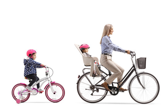Mother riding a bicycle with a child and girl riding behind