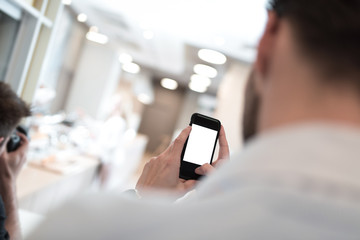 Businessman holding mobile phone in his hand trying to make a picture. Isolated cellphone screen.