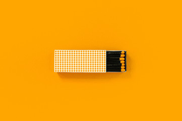 Black wood matches with yellow heads in creative dotted paper box on bold yellow background.