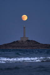 Incredible view of the full moon over the lighthouse of the small village of Cabo de Palos. Cartagena. Spain