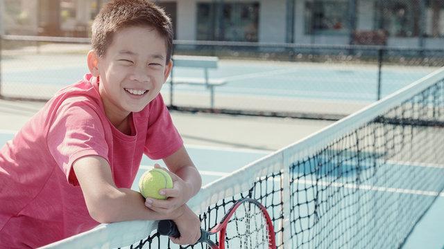 Young healthy and happy tween preteen multiethnic mixed Asian boy tennis beginner player on outdoor blue court, active child sport, student school camp