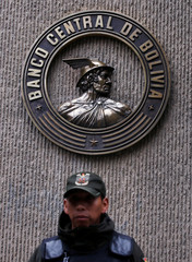 A guard stands in front of the logo of Bolivia's Central Bank in La Paz